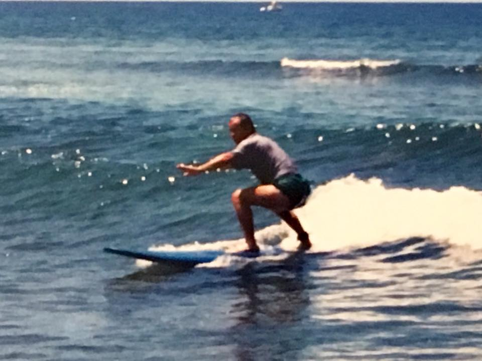 man on surfboard riding wave