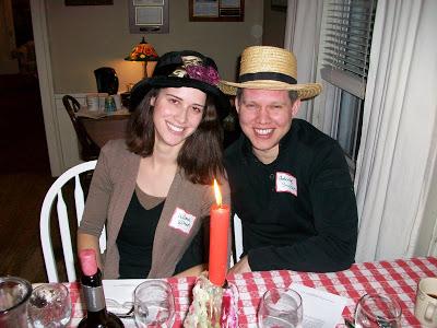 Woman and man wearing dress up hats near candle light
