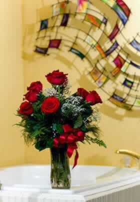 bouquet of a dozen red roses in a glass vase set on the edge of a jacuzzi tub with multicolored wall hanging