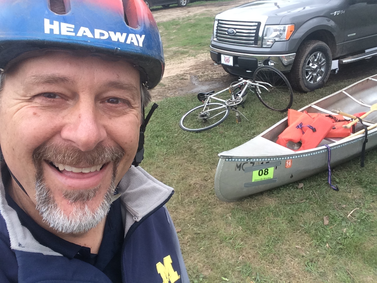 Smiling man wearing a blue bicyclist helmet with white bicycle and aluminum canoe with orange life preserver