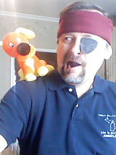 man with maroon headband and eye patch with an orange dog perched on his shoulder
