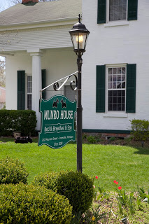 Munro House Green sign on lamp post surrounded by shrubbery in front of white business