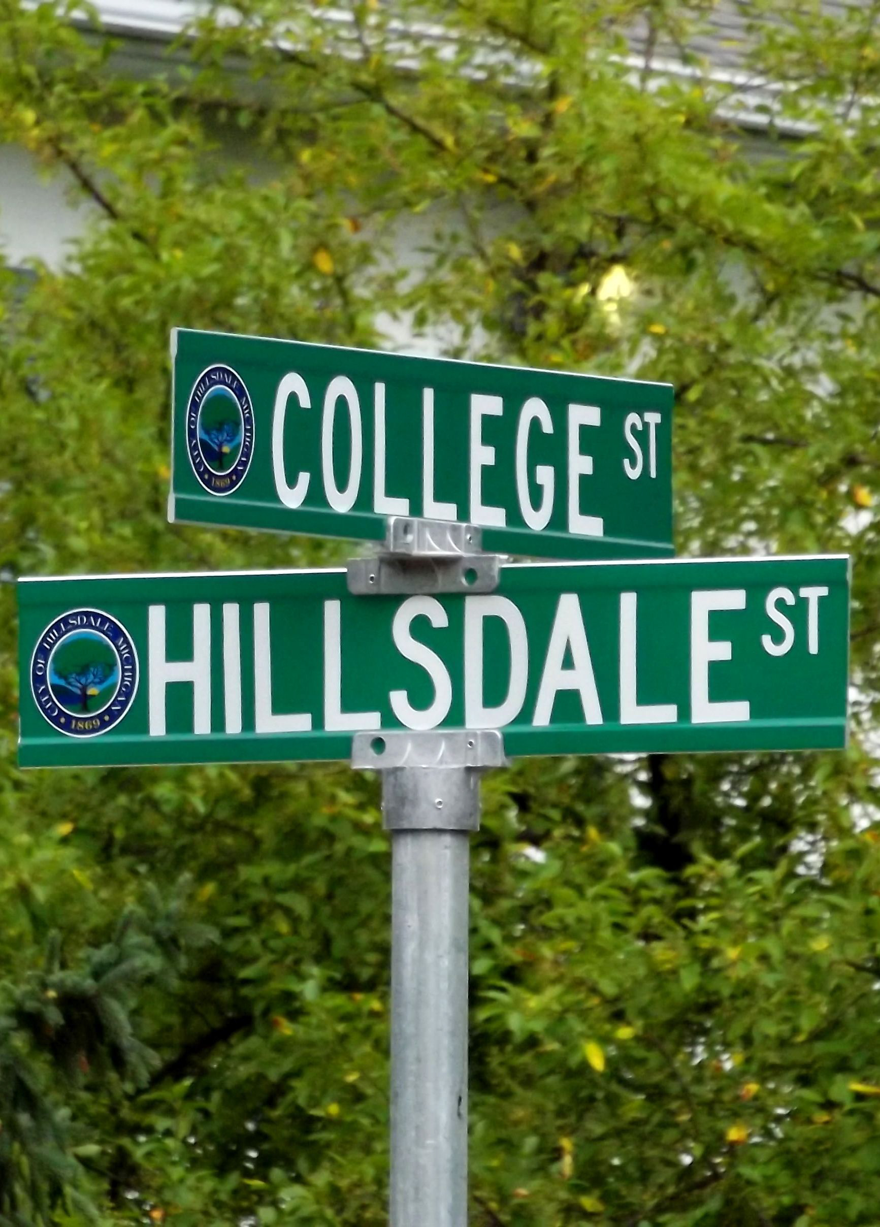 Green street signs with white lettering depicting the corner of College and Hillsdale streets