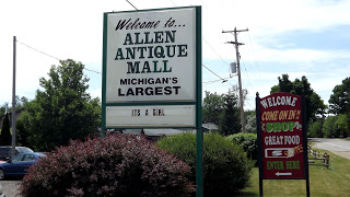 green and white welcome to allen antique mall sign