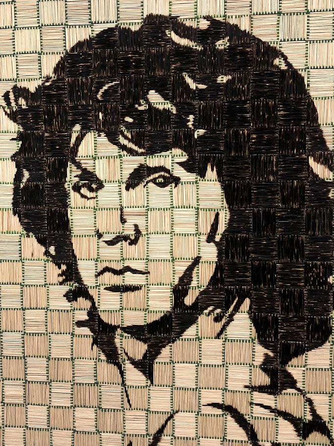 a patchwork of matchsticks with green tips that create a portrait of rock star Jim Morrison