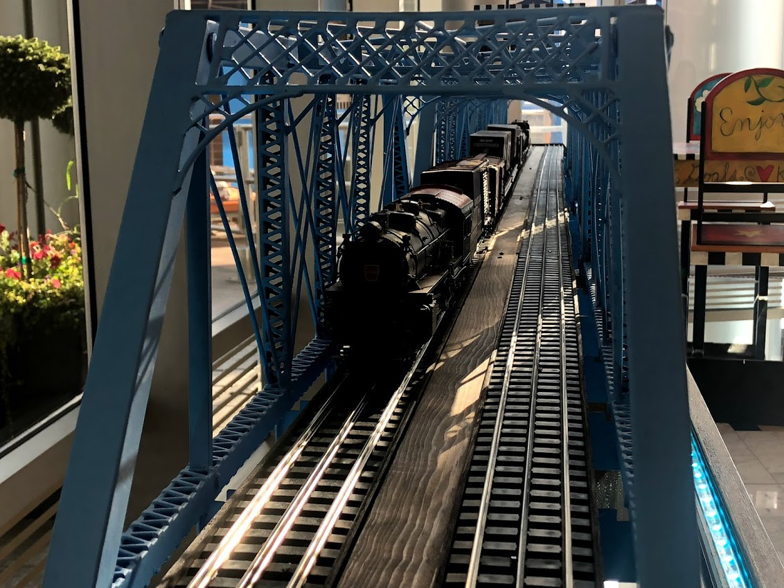 a small scale of a locomotive train crossing a blue bridge