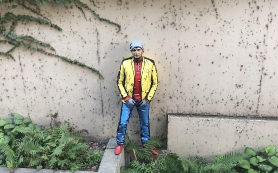 a cartoon man wearing a yellow coat and blue jeans standing by a wall in a garden