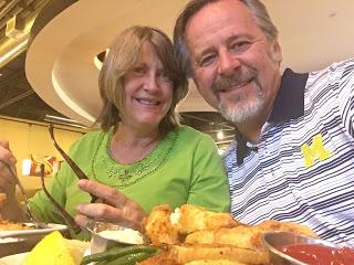 White couple in seafood restaurant, woman in green shirt, man in striped Michigan Logo shirt