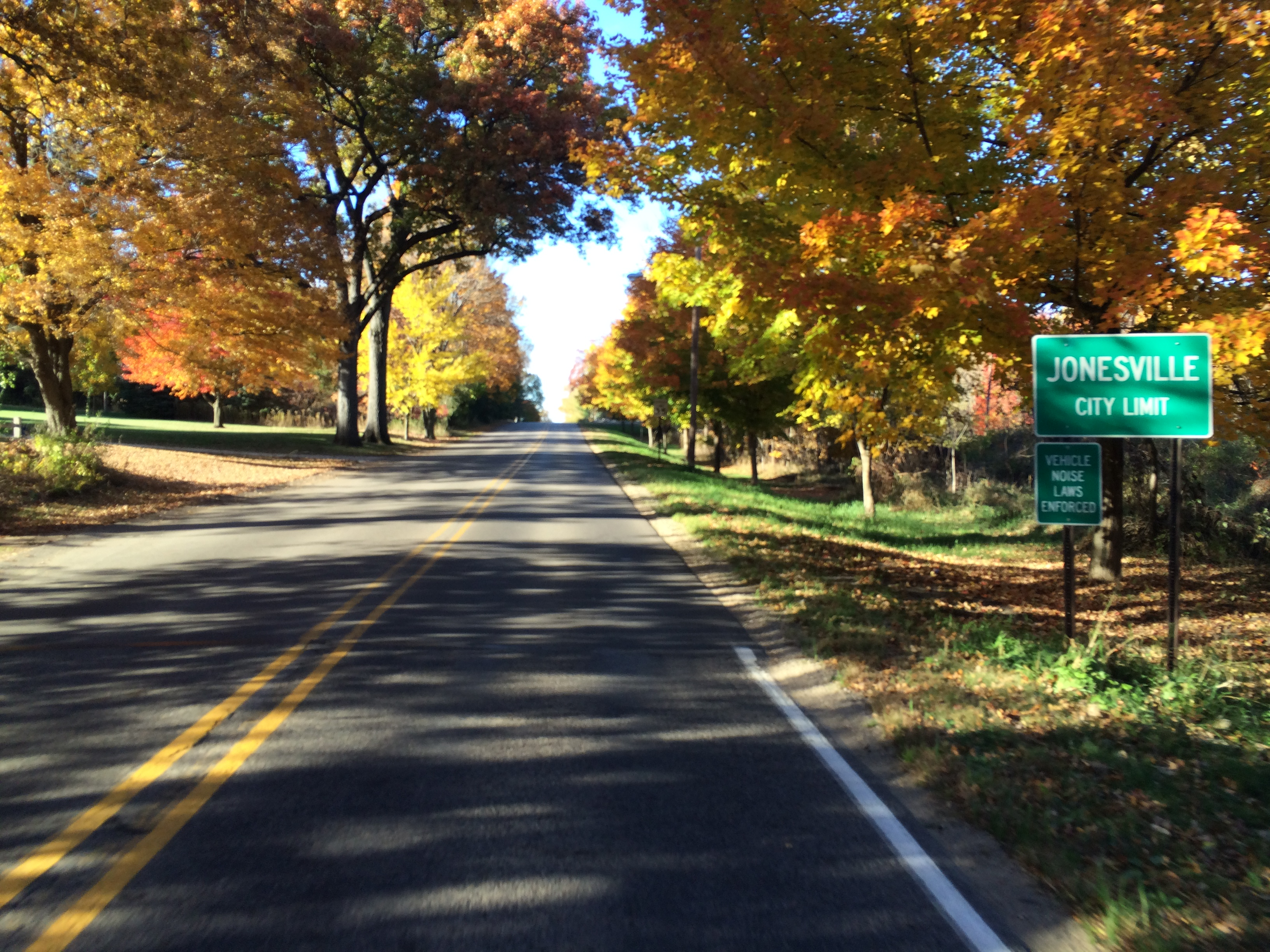 Blacktop road with yellow centerline surrounded by trees in brilliant fall colors of yellow and orange with a green Jonesville City Limit sign
