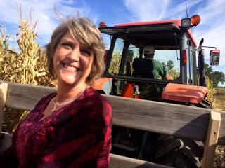 Smiling lady in red riding in a tractor pulled wagon through a corn field
