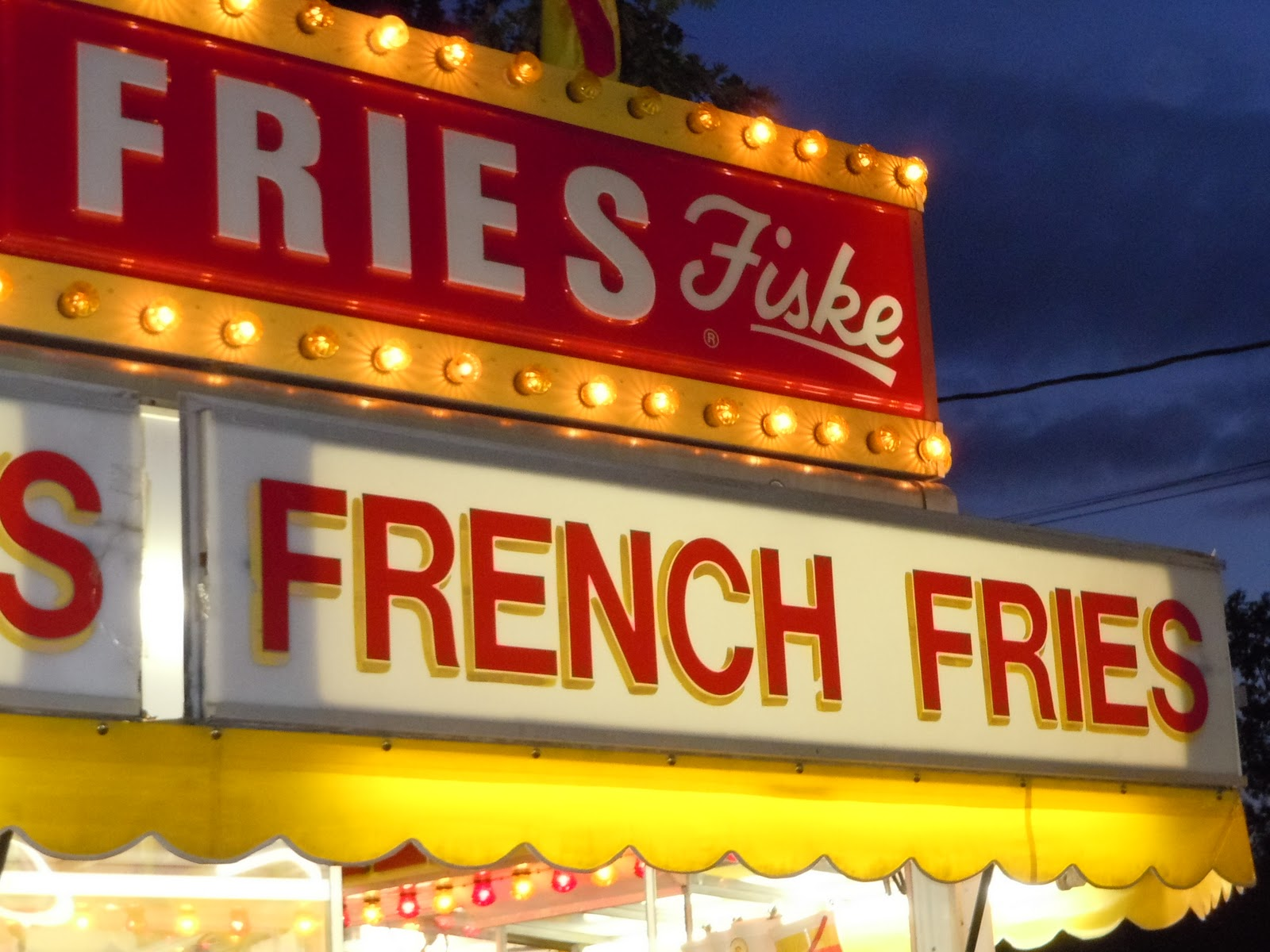 Night view of fair signs advertising Fiske French Fries