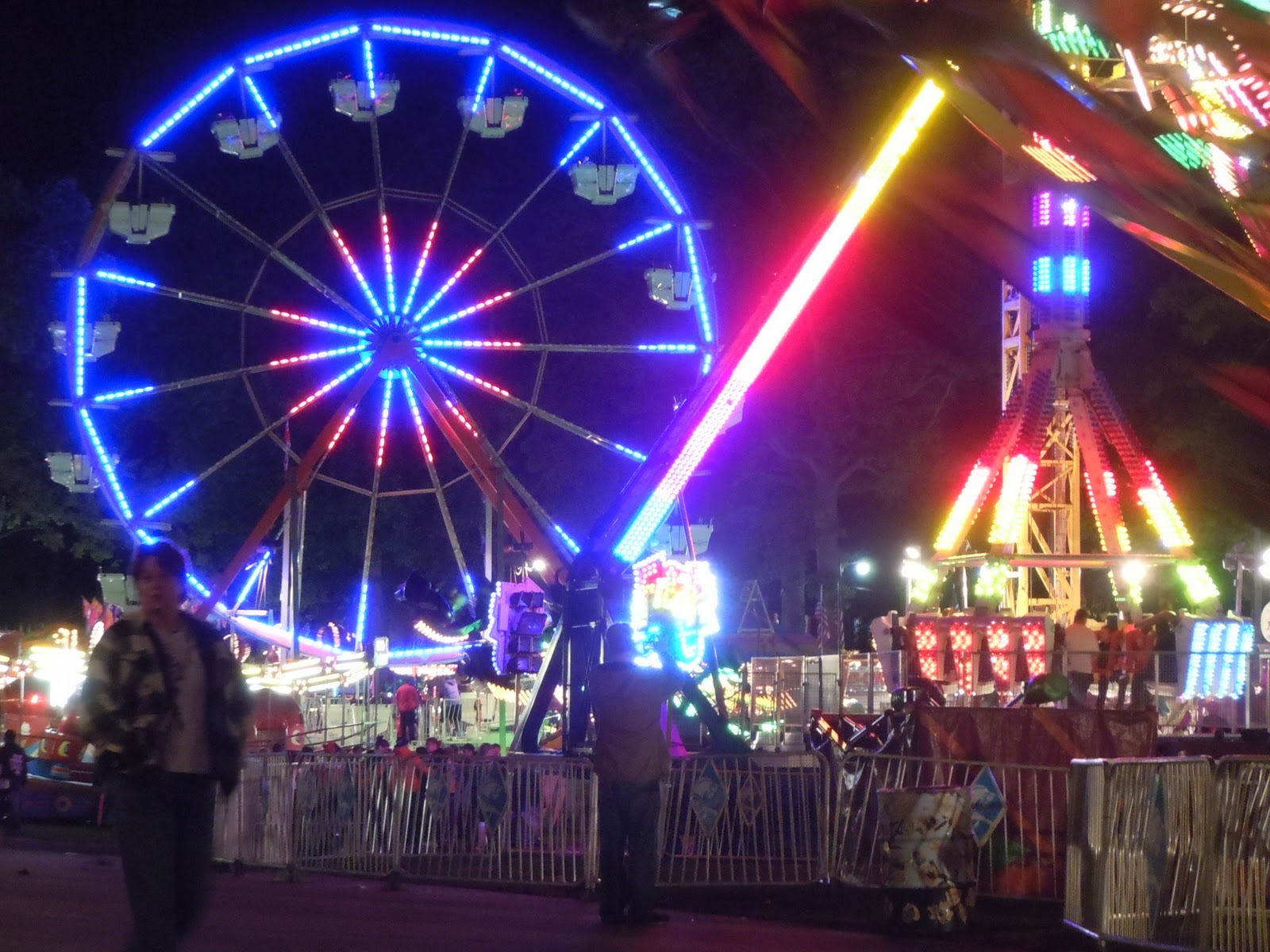night view of carnival rides including Ferris Wheel in blue lights
