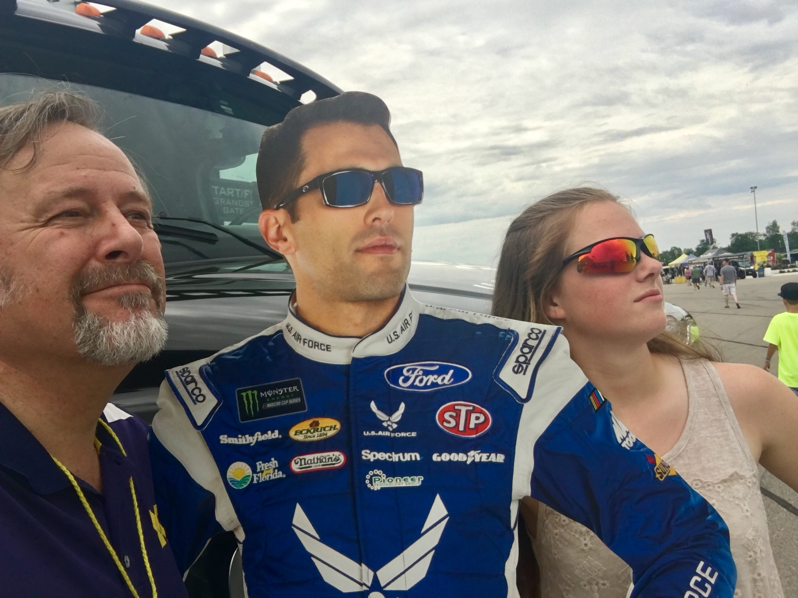 man and woman flanking cutout of nascar driver in uniform