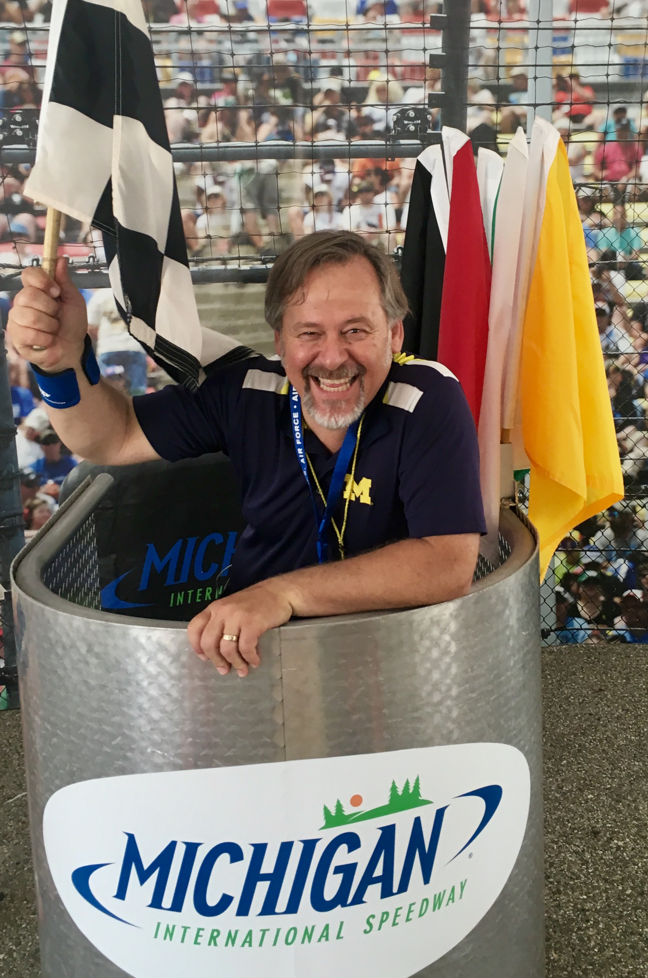 man in a blue shirt holding a checkered flag while standing in a michigan international speedway booth