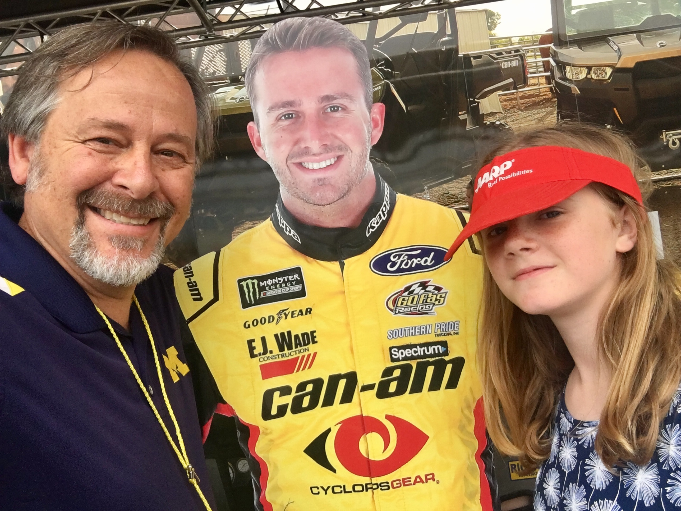 Man and girl with a red hat posing with cutout of nascar driver in yellow sponsor uniform