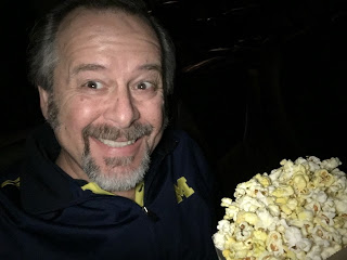 dark theater with man in blue shirt enjoying a large bag of popcorn