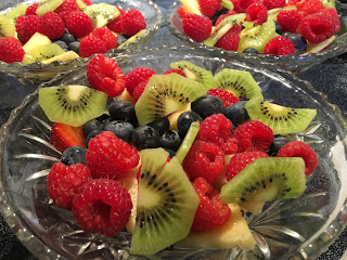 Fresh fruit bowl with red raspberries blueberries pineapple green kiwi