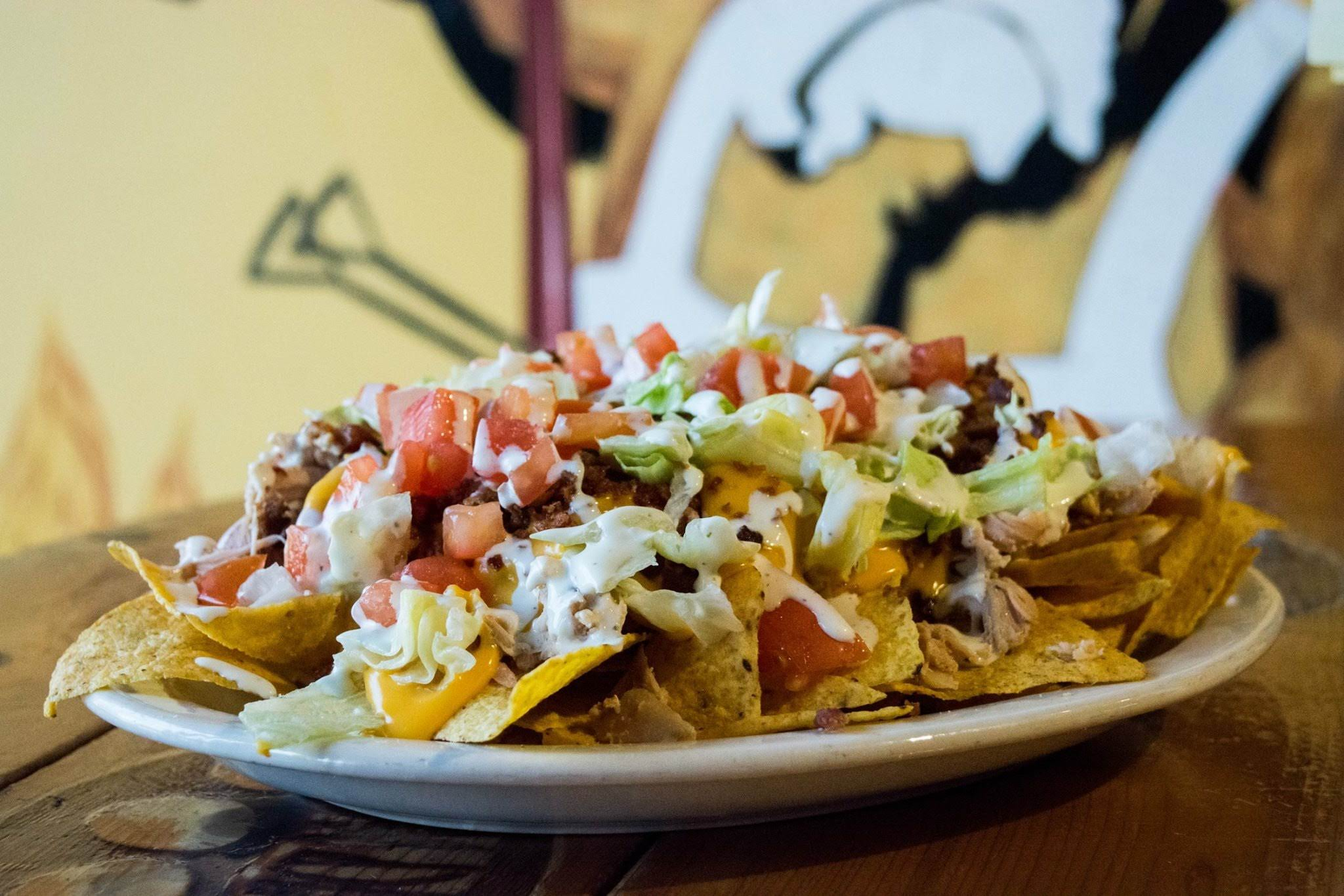 A plate of nachos with red tomatoes, cheese, lettuce, and pulled pork
