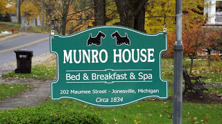 Green bed and breakfast sign with Scottish Terrier mascots amidst fall colors