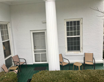 Large porch with screen door access, white columns, four chairs, and two tables partially hidden behind hedge