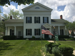 American flag flying outside white greek revival style home