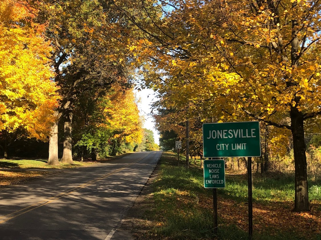 green city limits sign on a road with trees of yellow leaves