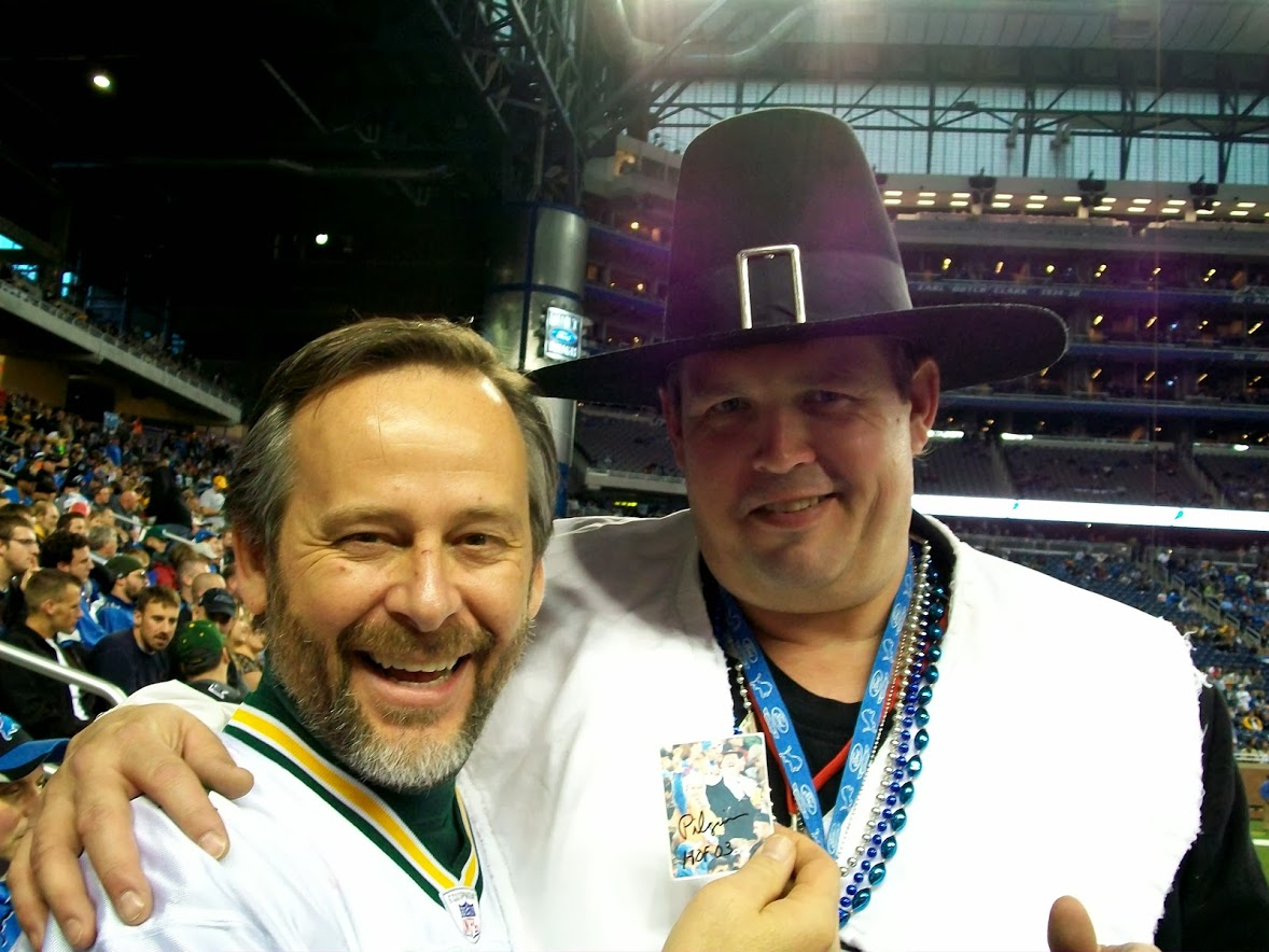 two men at Ford Field in Detroit. one wearing a football jersey, the other in a Pilgrim costume