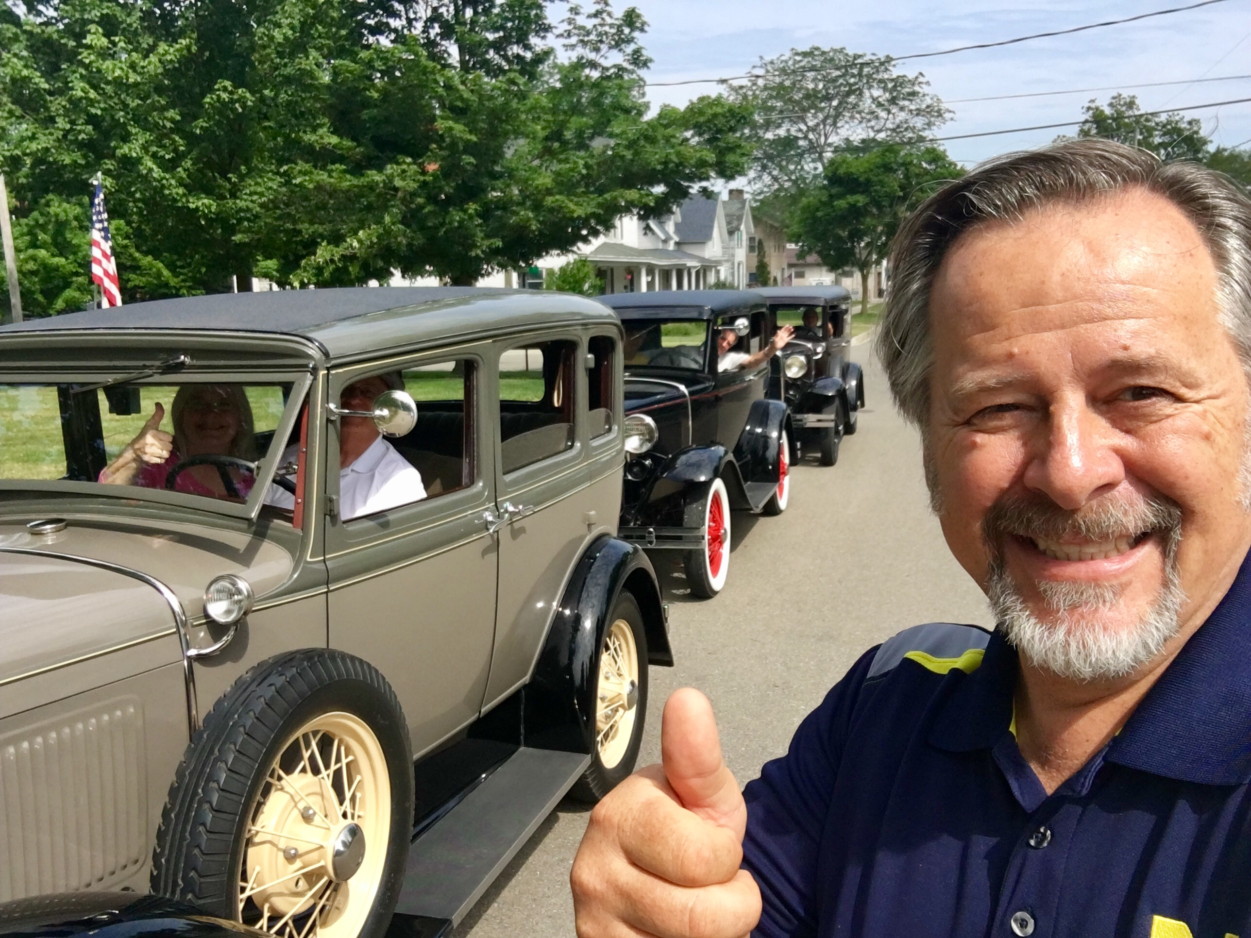 Model T automobiles behind man in blue shirt