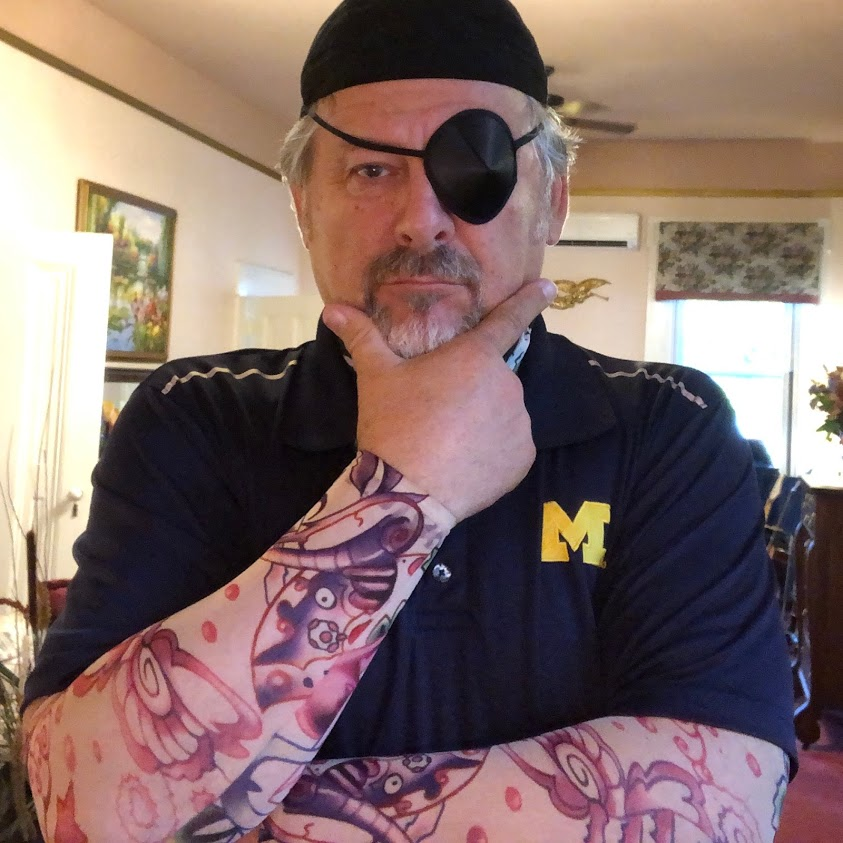 man with black dew rag, eye patch, and tattoo sleeves wearing a Michigan M shirt