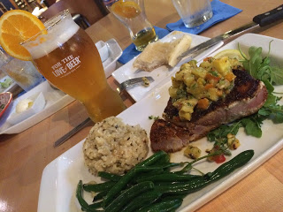 Rectangular white food plate with garnished steak, green beans, and rice beside a glass of beer with an orange slice
