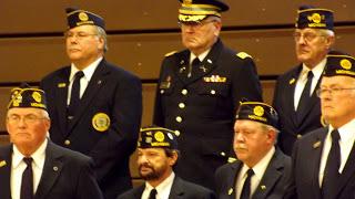 Veterans in uniform at attention during veterans day program