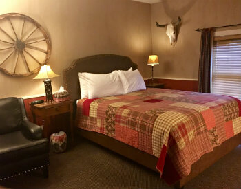 red plaid patchwork quilt comforter, four pillows on queen size bed with leather studded headboard, adjacent black leather studded chair, end tables with lamps, plus decorative wagon wheel and steer skull mount on wall