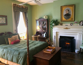 formal bedroom with green walls and comforter and white mantel fireplace