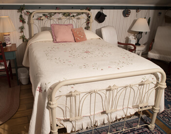 colonial style bedroom with white bed spread and decorative white iron bed frame