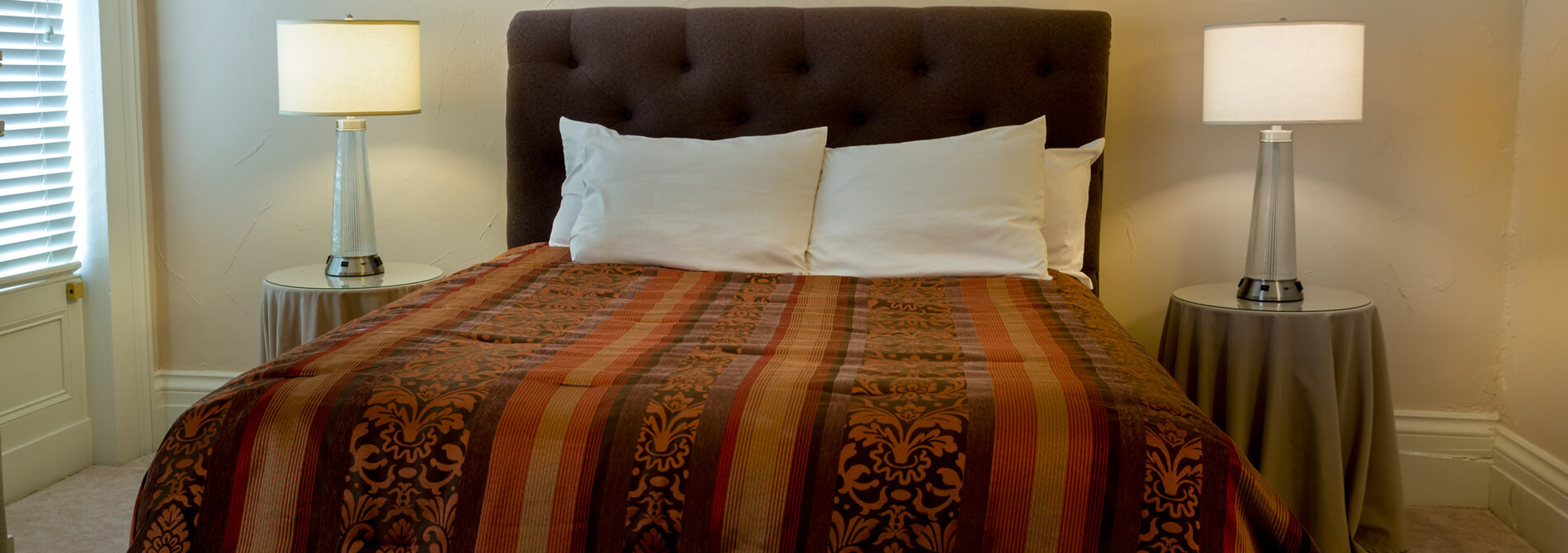 modern bed in sleek bedroom with brown striped comforter and two end tables with lamps