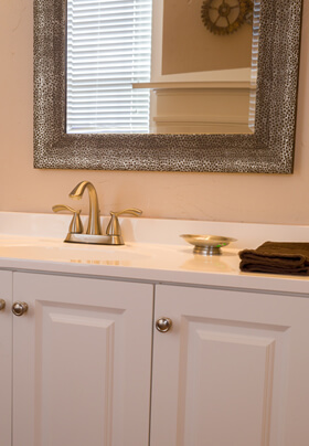 white bathroom vanity with gold fixtures brown hand towel and pewter hammered mirror frame