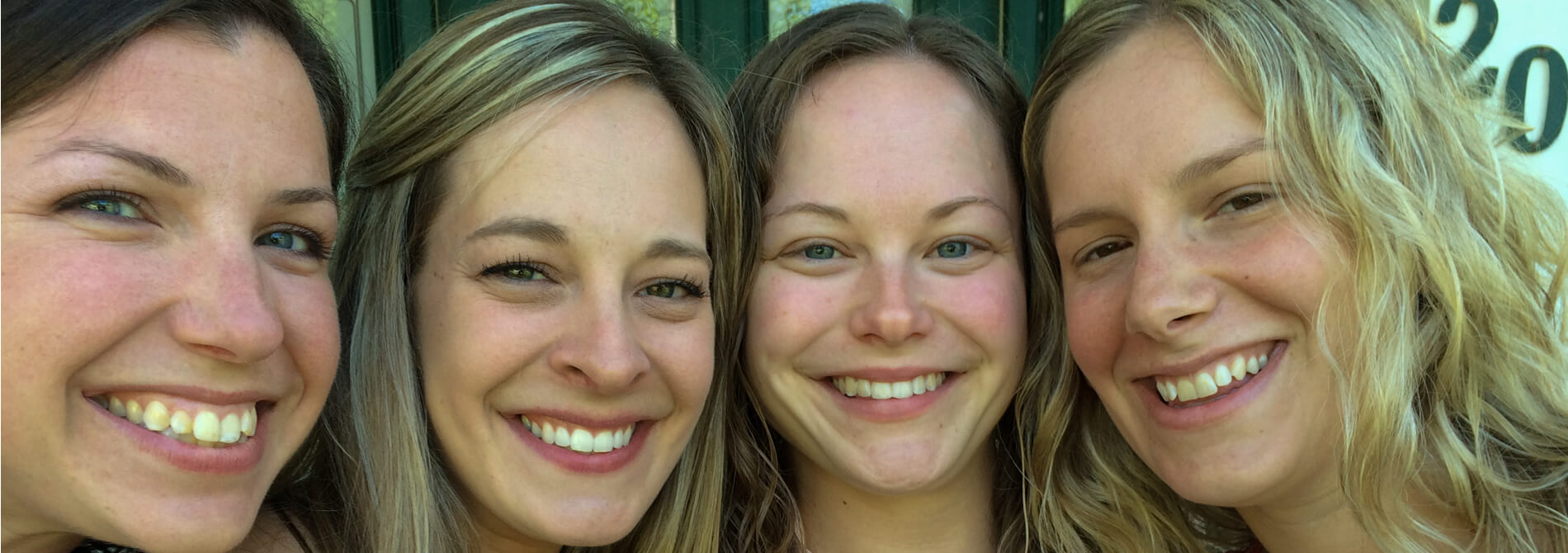 four young women with big smiles cheek to cheek dressed in red white and blue on front porch