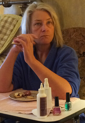 woman in blue robe at a table enjoying snacks while waiting for a manicure