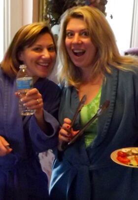 two young women in blue robes enjoying water and veggies during a spa day break