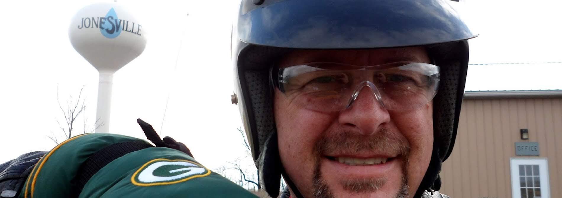 biker wearing helmet and green gloves in front of jonesville water tower