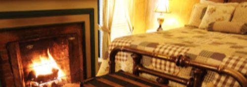 plaid bedspread on brass bed with lit fireplace