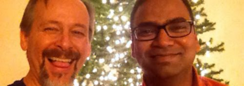 2 guys in front of christmas tree