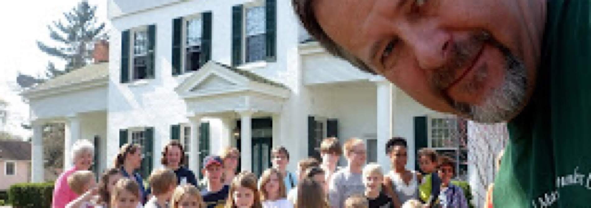man with many kids in front of big old white house