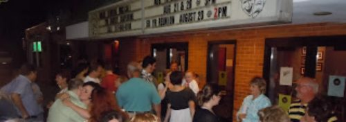 crowd gathering outside theater with marquee