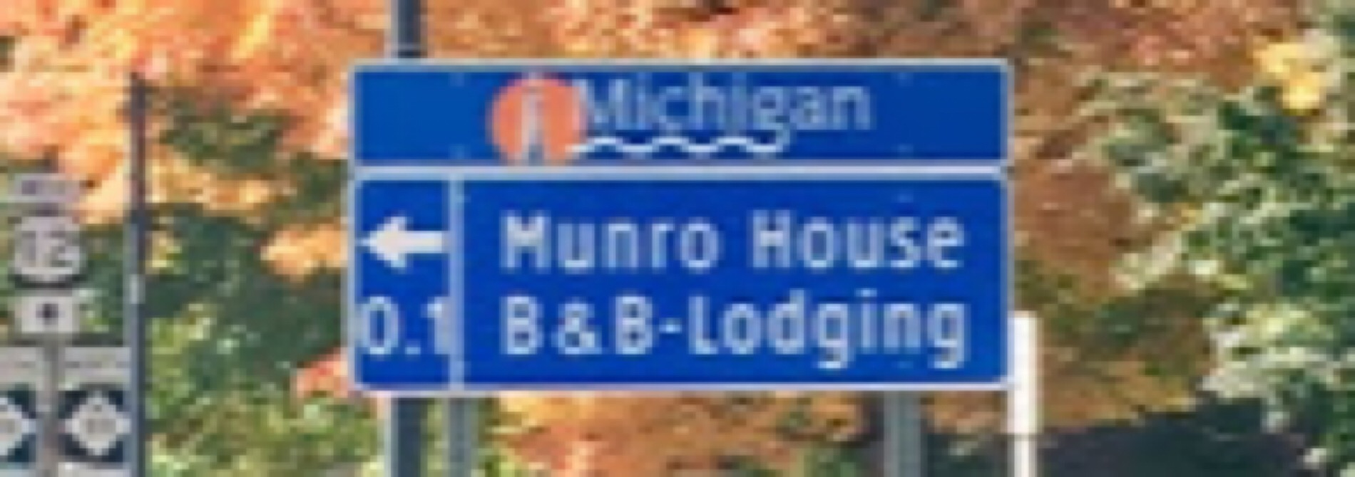 blue highway sign with fall colors in background