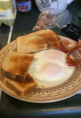 typical breakfast choice includes eggs over easy bacon and toast on brown and cream plate