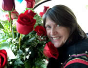 woman with black and red jacket holding a red rose floral bouquet