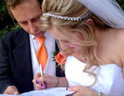 Man in black tuxedo with white vest and orange tie and woman in white wedding gown signing papers