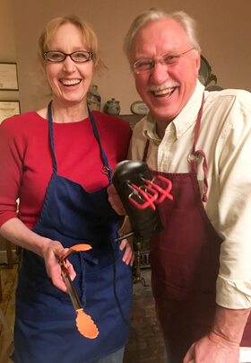 woman with glasses wearing red shirt and blue apron man wearing white shirt and maroon apron with kitchen utensils
