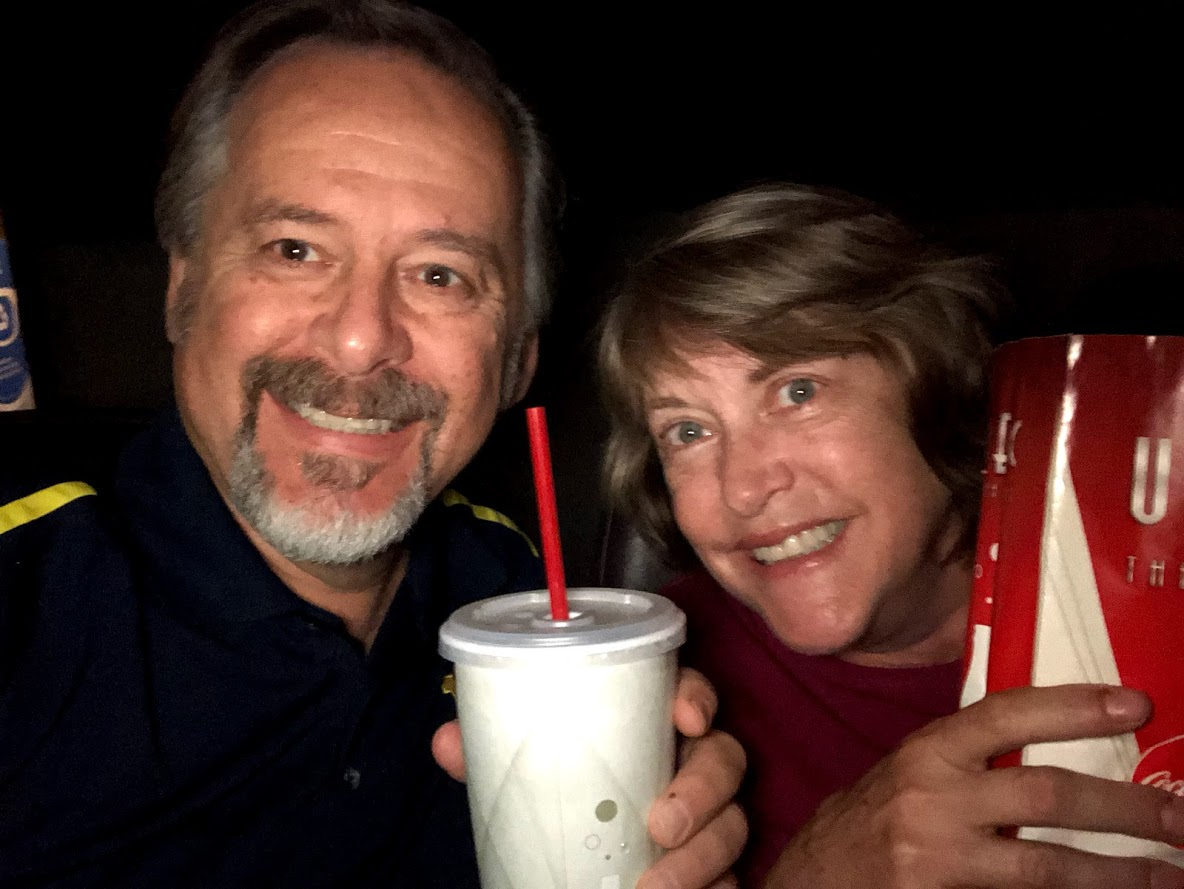 man and woman in a darkened theater holding drinks and popcorn